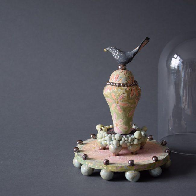Keramiek sculptuur, miniatuur van ca 20 cm. Aardewerk, ook het plateau en de pootjes. Bewerkt met verschillende engobes en glazuren. Mede geïnspireerd op de serie ' Keeping up appearances' met Mrs. Hyacinth Bucket / Bouquet