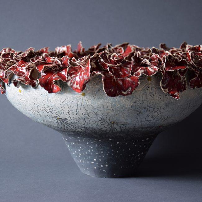 Keramiek schaalvorm. Aardewerk opgebouwd uit ringen met een rand van handgevormde bloemvormen. Bewerkt in meerdere lagen met engobes en glazuren.