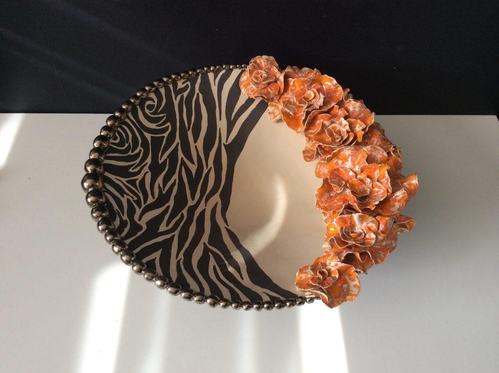 keramiek. Aardewerk schaalvorm opgebouwd uit ringen. De rand bestaat uit bolletjes en bloemvormen, stuk voor stuk met de hand gemaakt. Bewerkt met engobes en glazuren.