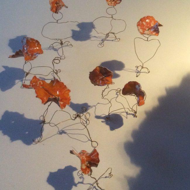 Aardewerk 'blaadjes', geglazuurd, met messingdraad gevormd tot figuren.