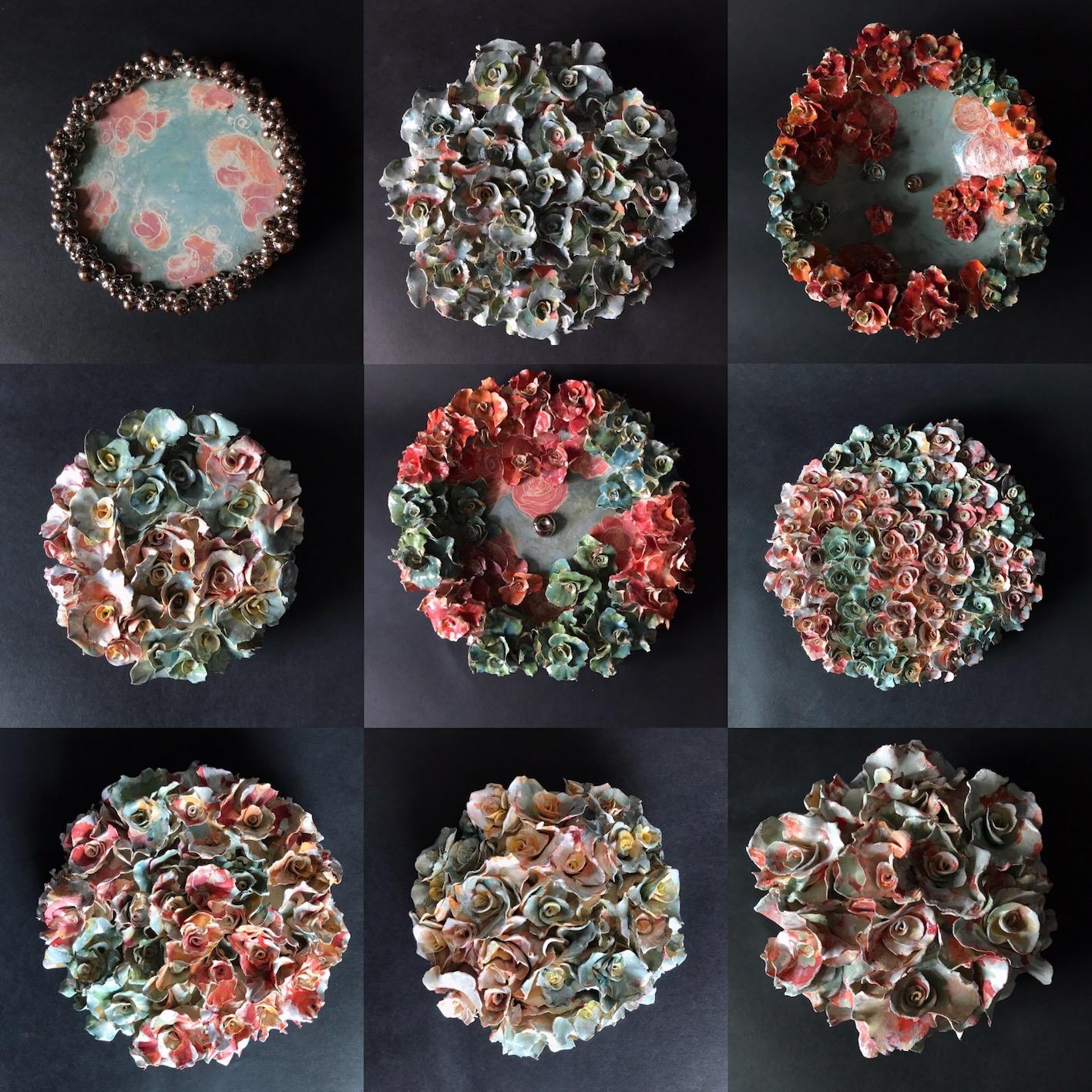 Keramiek kunst voor aan de muur. Aardewerk, ronde vormen bedekt met handgevormde bloemvormen. Bewerkt met engobes en glazuren.